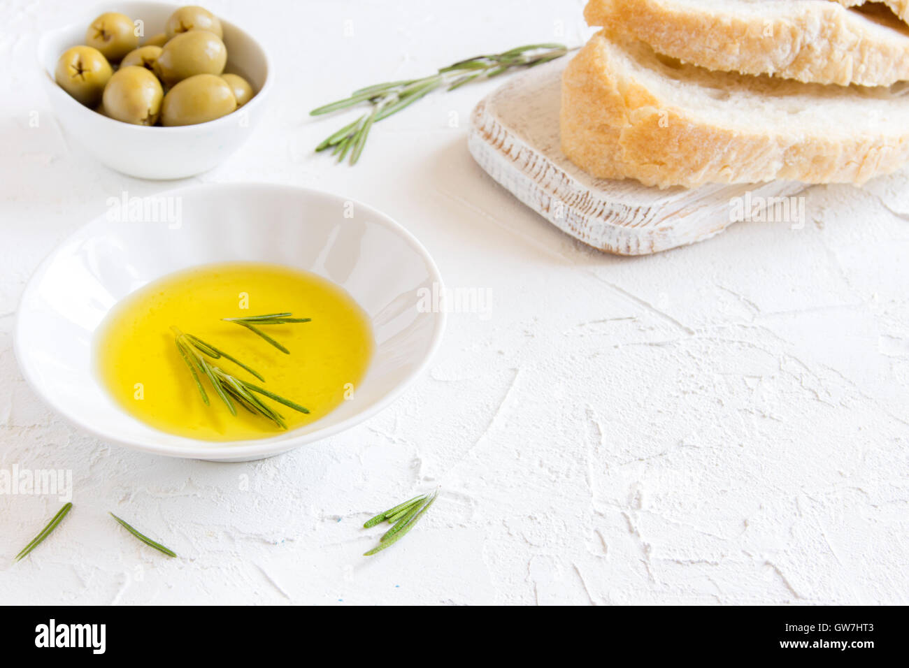 Organic olive oil with rosemary and bread over white stone background with copy space, healthy food concept - Stock Image