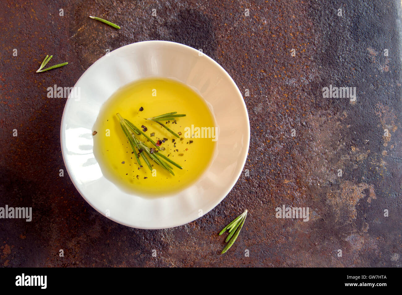 Organic olive oil with rosemary and spices over rustic metal background with copy space, healthy food concept - Stock Image