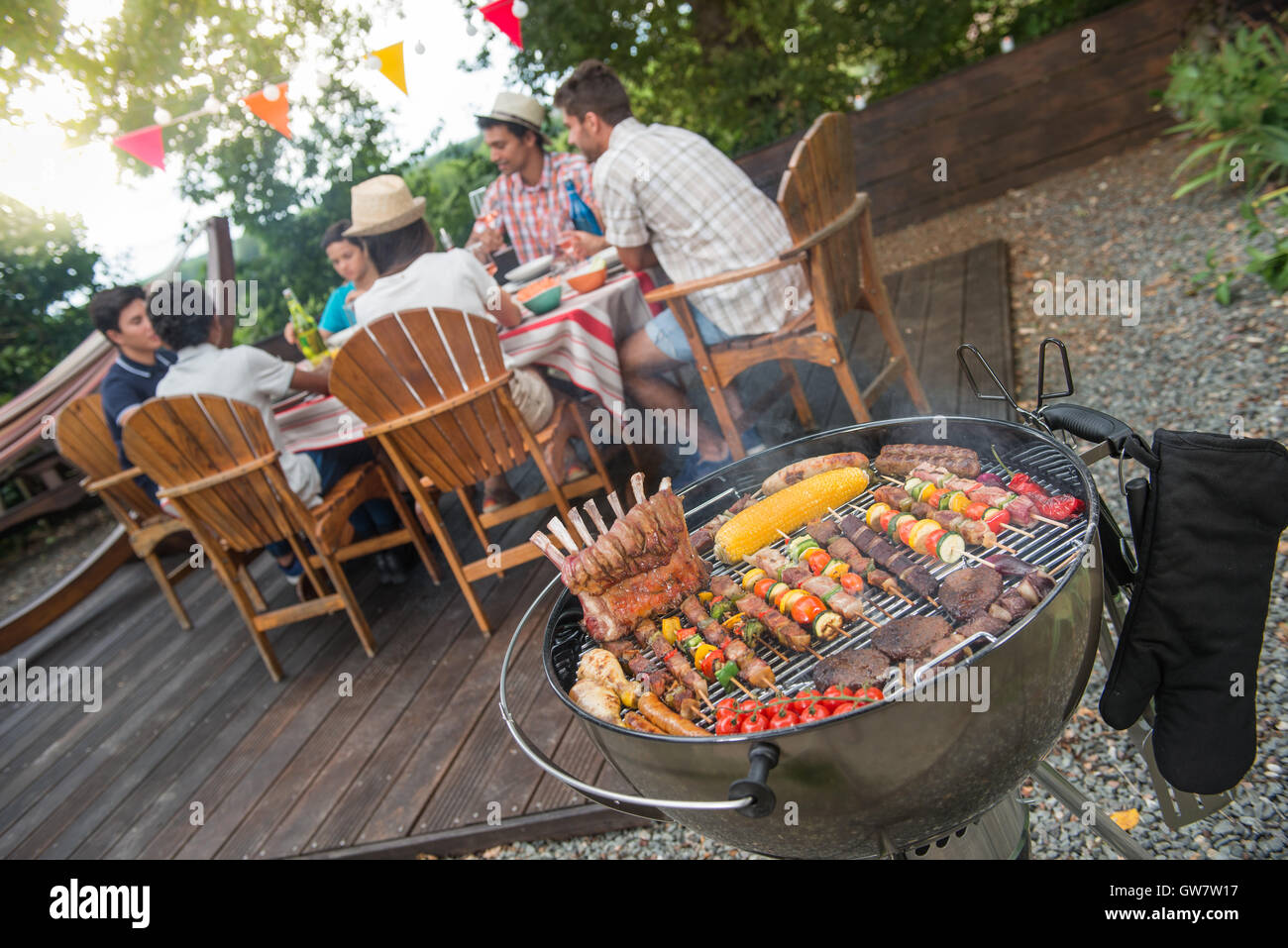 man grilling meat on garden barbecue party in the background friends stock photo 118801907 alamy. Black Bedroom Furniture Sets. Home Design Ideas