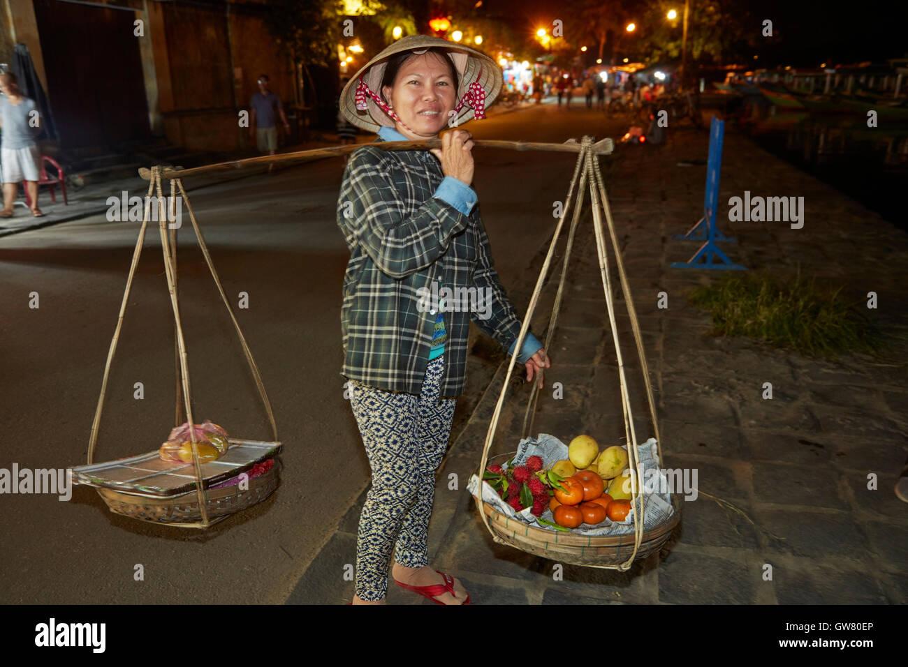Vietnamese woman carrying produce on a bamboo yoke, Hoi An (UNESCO World Heritage Site), Vietnam - Stock Image