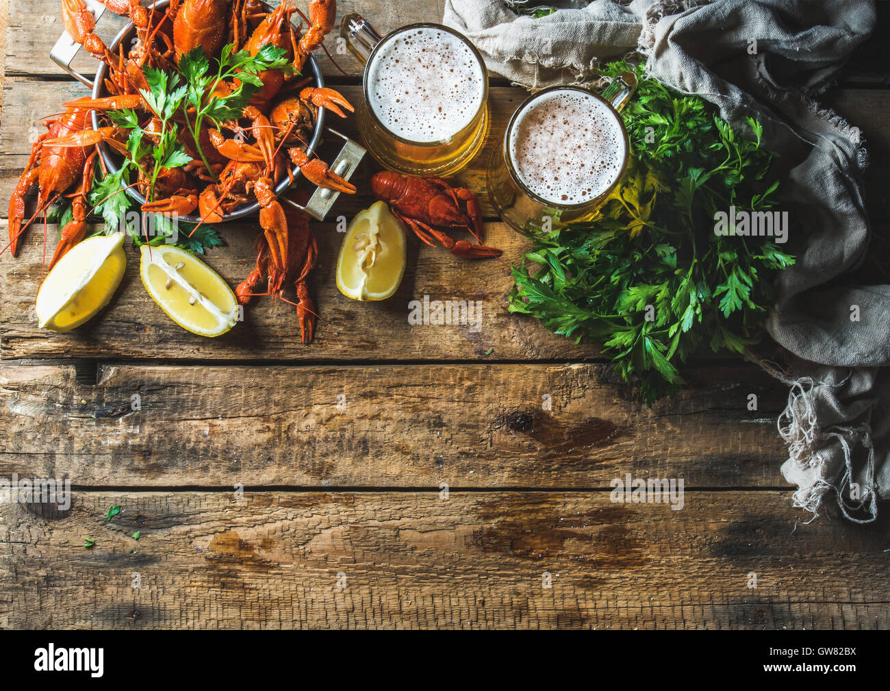 Wheat beer and boiled crayfish over old wooden rustic background - Stock Image