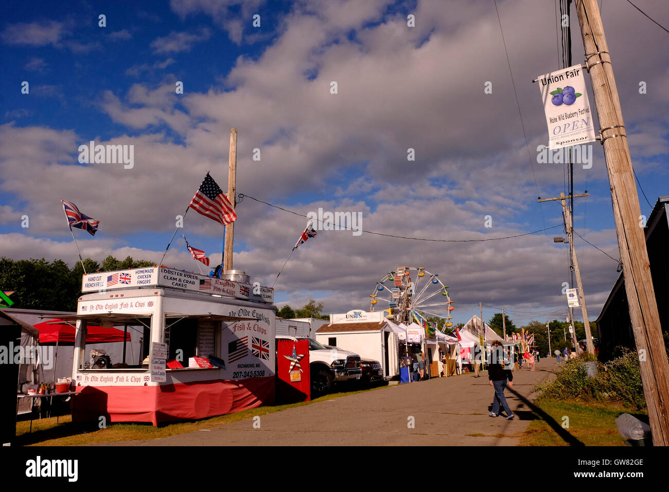County fair midway with ferris wheel, rides and food stalls Stock Photo
