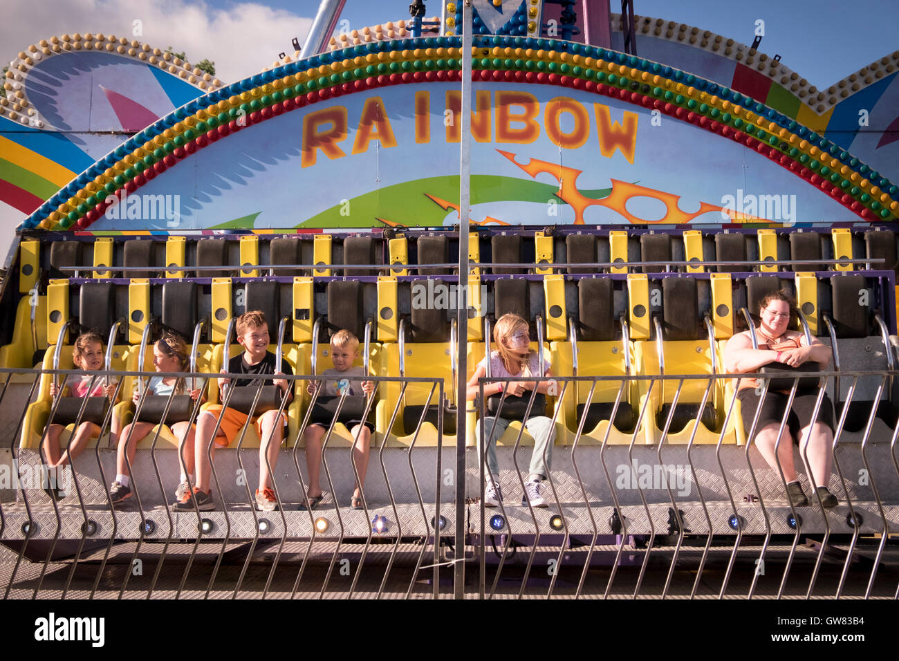 Six children await the start of a sideshow ride at a country fair - Stock Image