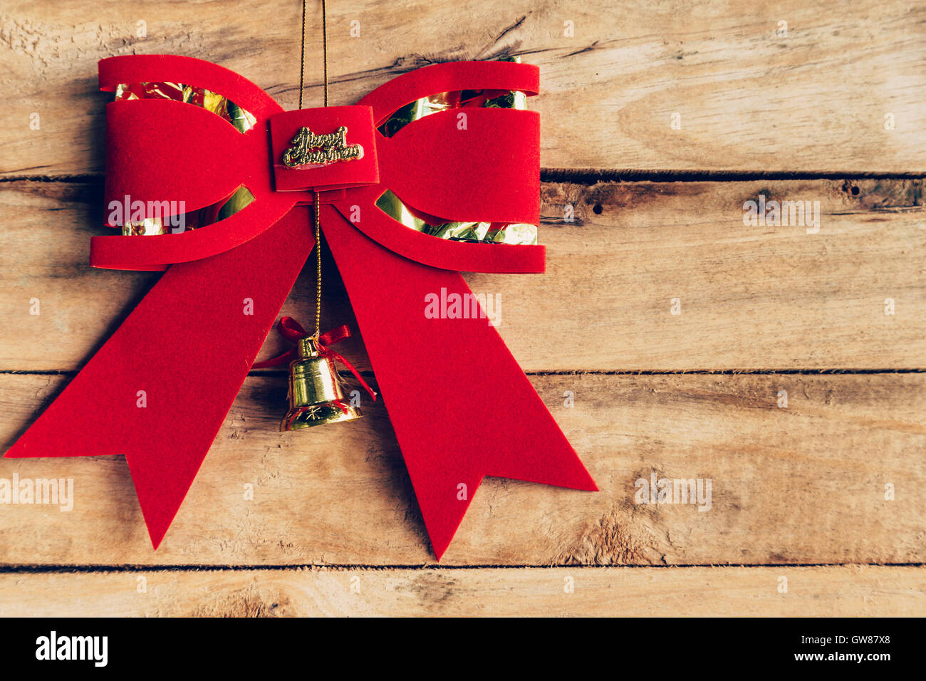 Red bow christmas hanging on wood background with copyspace. - Stock Image