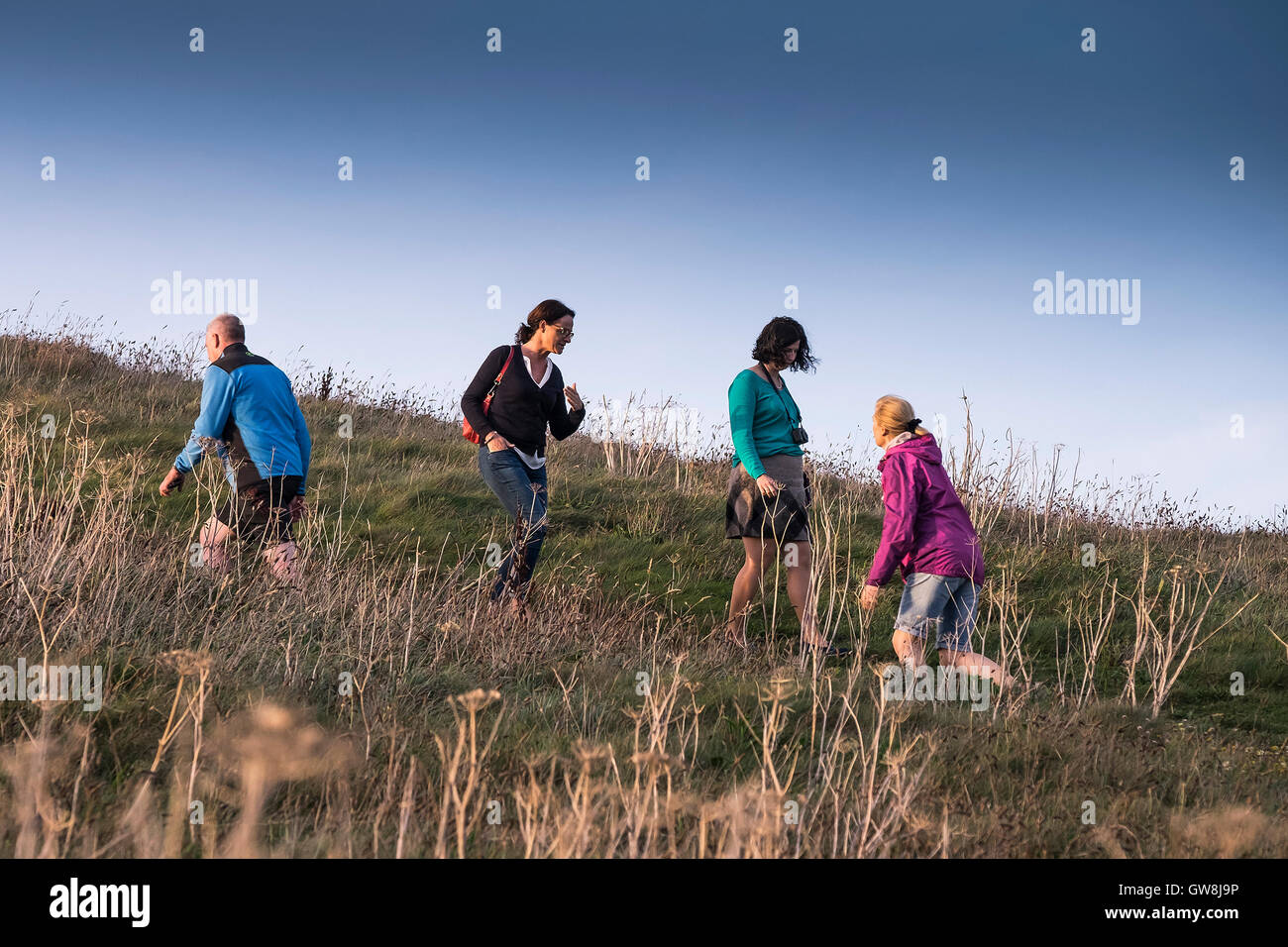 People walking up and down a hill on Towan Head in Newquay, Cornwell. - Stock Image