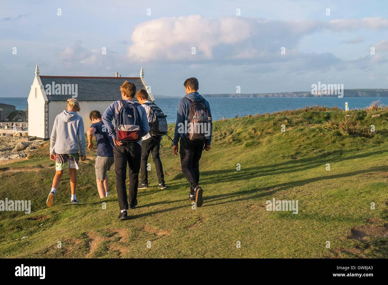 Fiver teenage boys walking towards Towan head in Newquay, Cornwall. - Stock Image