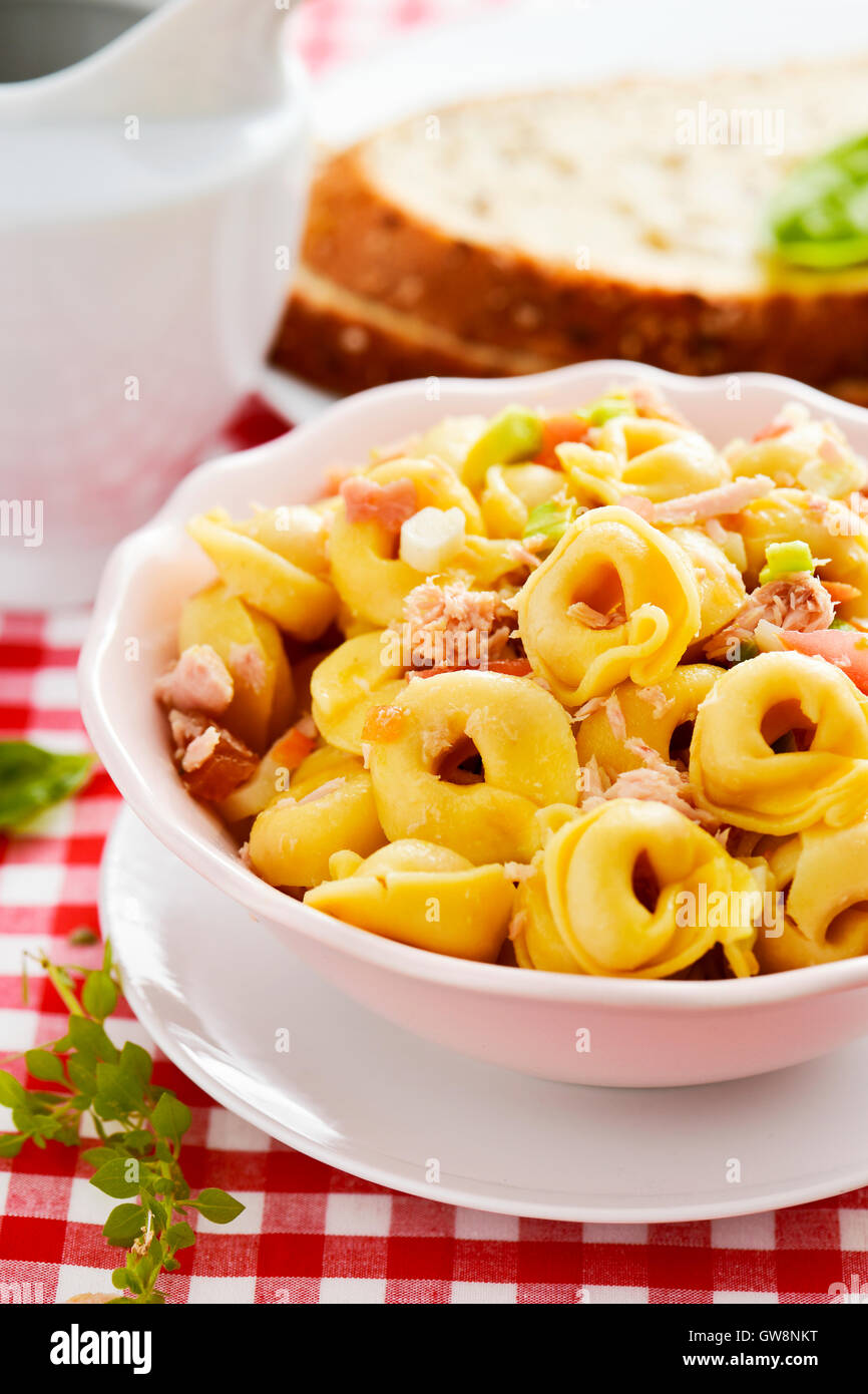 closeup of a ceramic bowl with a pasta salad made with tortellini on a table set with a red and white checkered - Stock Image