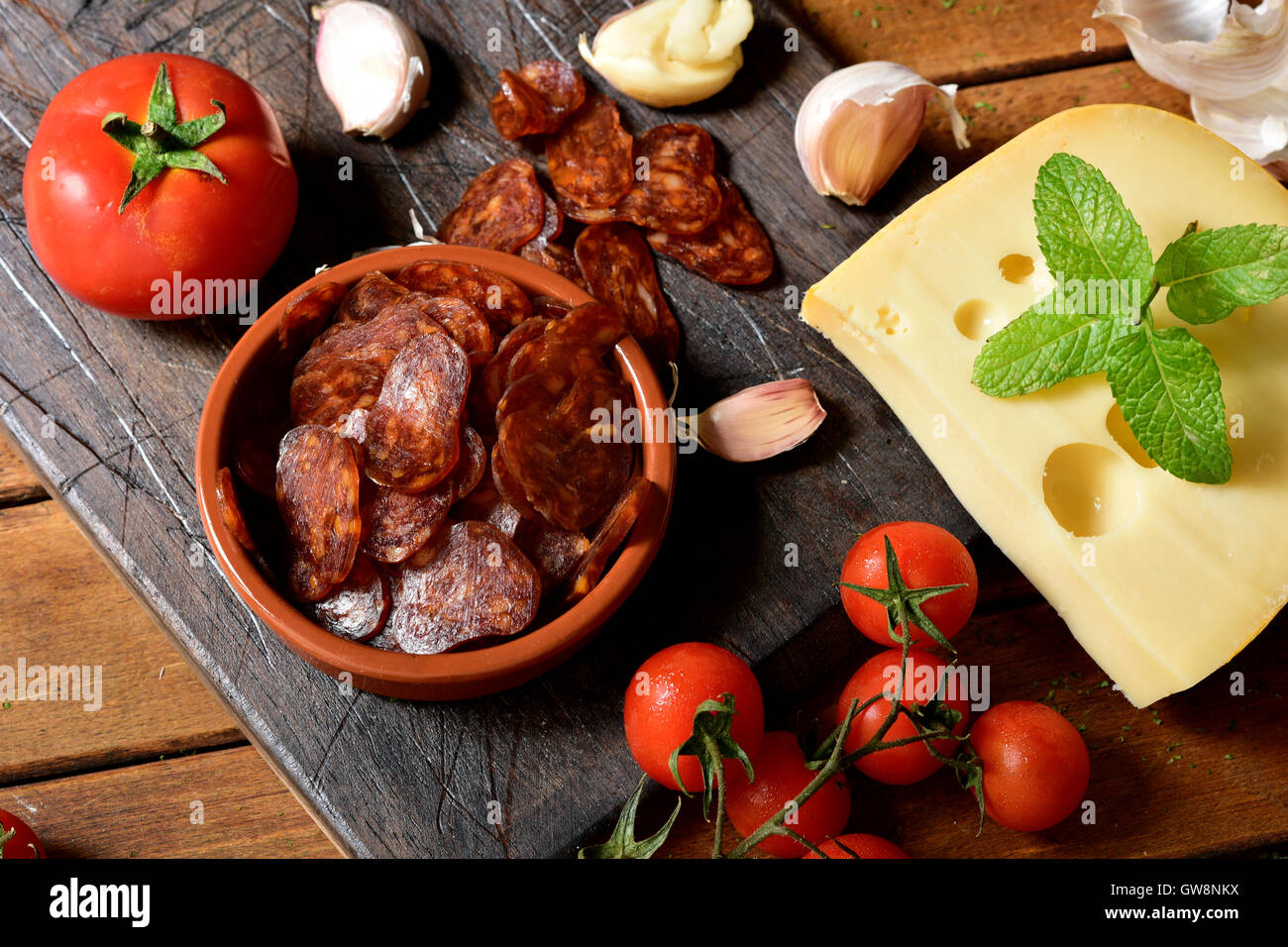 high-angle shot of an earthenware bowl with some slices of Spanish chorizo, a pork sausage typical of Spain, on Stock Photo