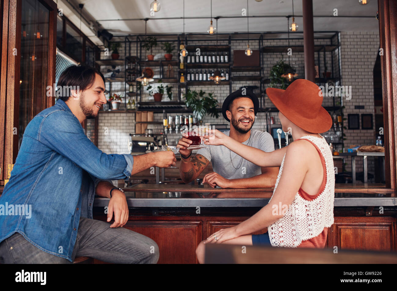 Young friends at cafe toasting drinks while sitting at a table. Three young people, two men and a woman meeting in a coffee shop Stock Photo