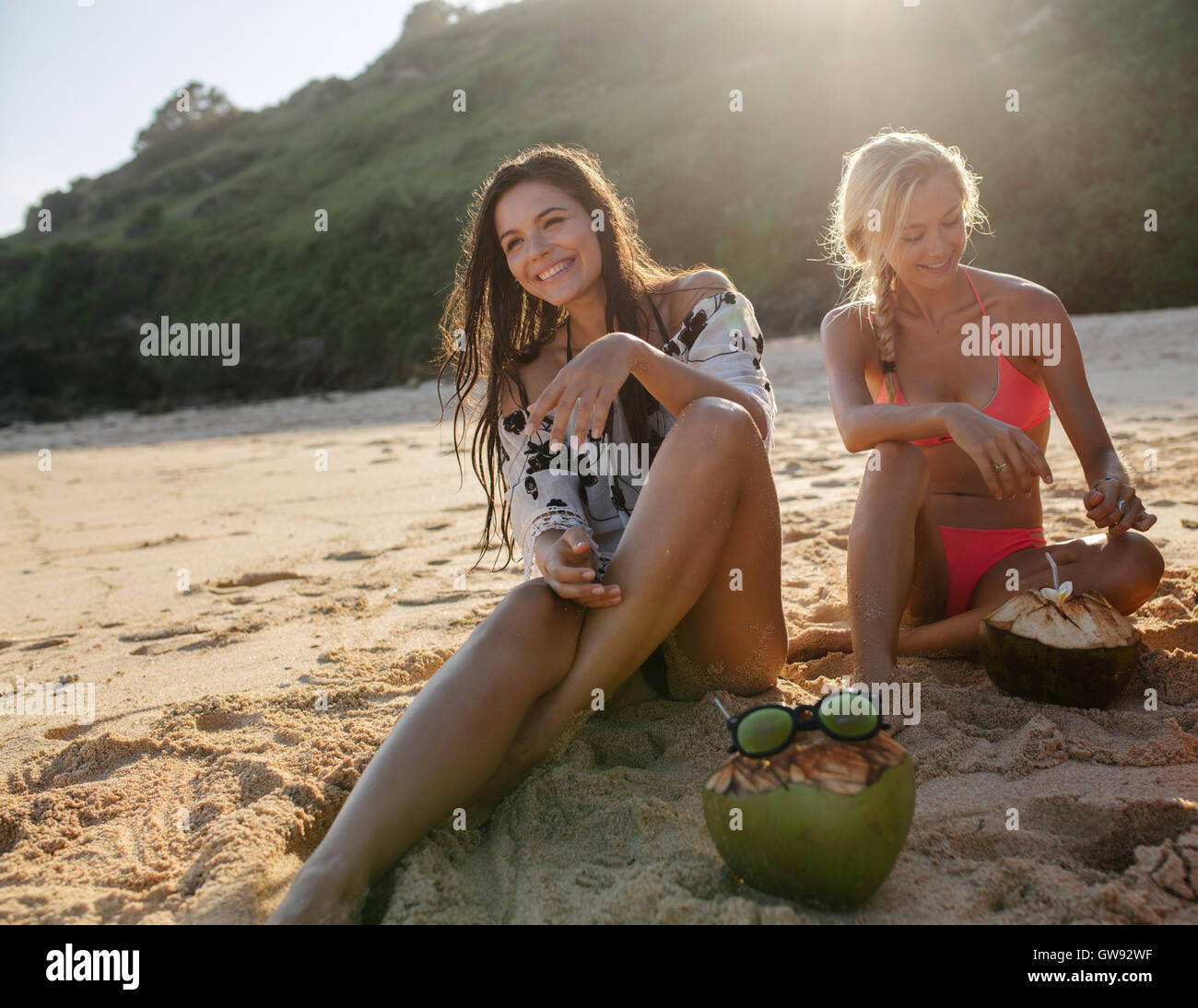 Two young women sitting on the sea shore and smiling. Female friends relaxing on the beach with coconuts on sand. - Stock Image