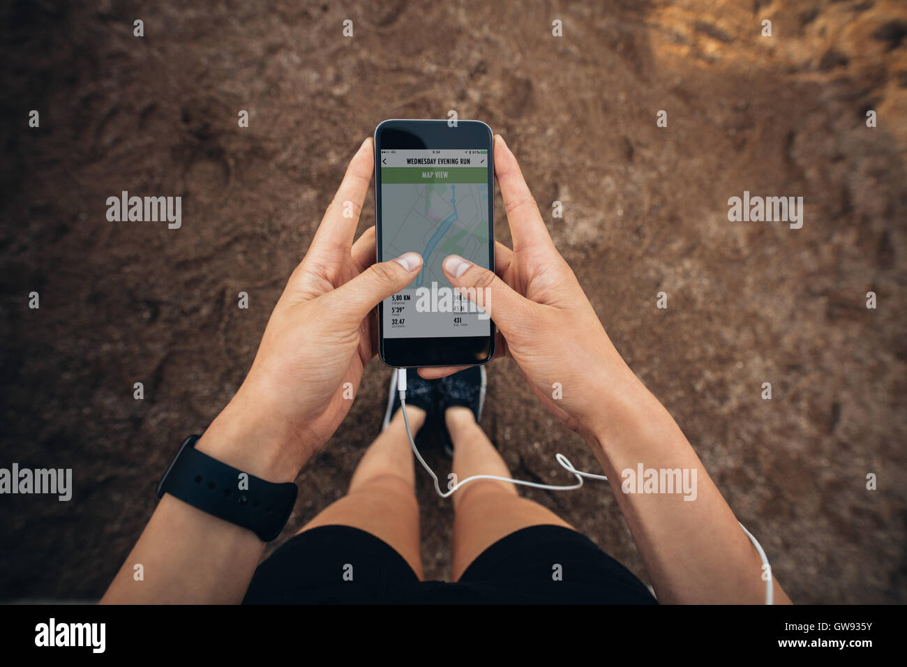 Woman checking the summary of her run on smartphone. POV shot of woman runner using a fitness app on her cellphone. - Stock Image
