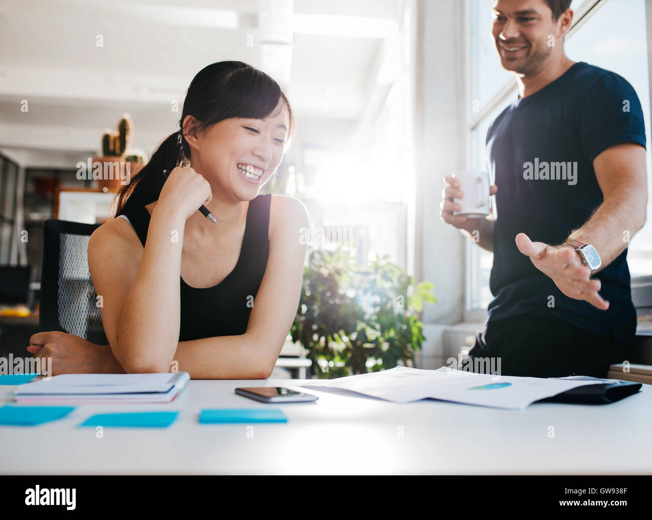 Shot of two young business partners discussing new ideas and smiling. Young people working together in office. - Stock Image