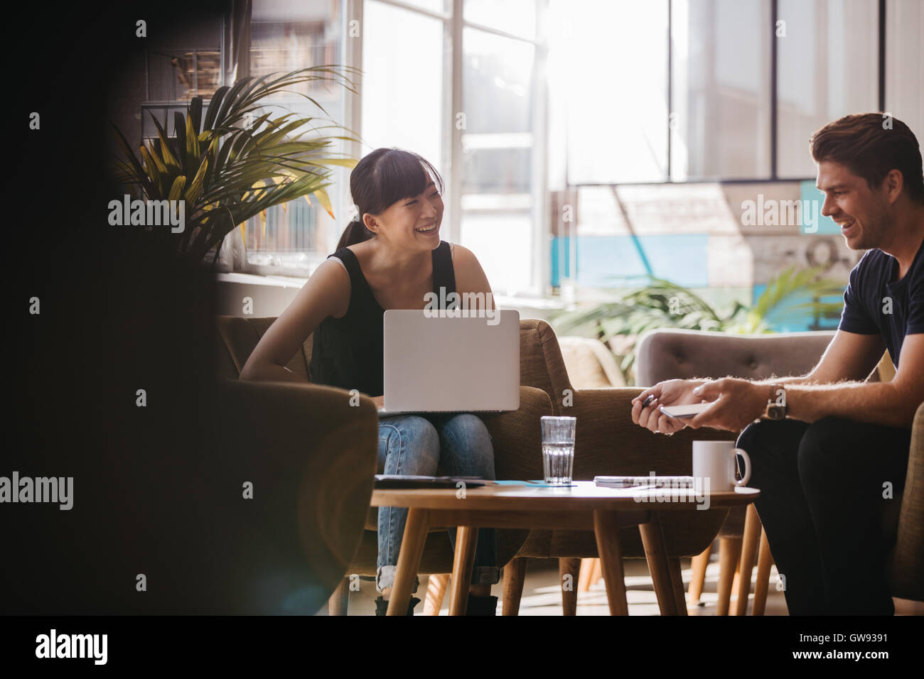 Shot of two business partners sitting in office lobby and smiling. Woman with laptop discussing business ideas with - Stock Image
