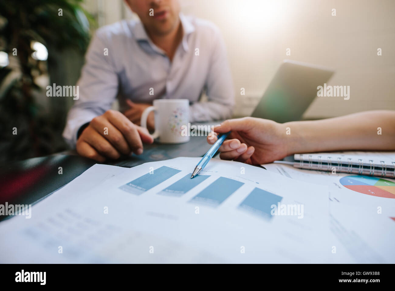 Close up shot of coworkers reviewing paperwork together in office. Businesspeople analyzing graphs during a meeting. Stock Photo