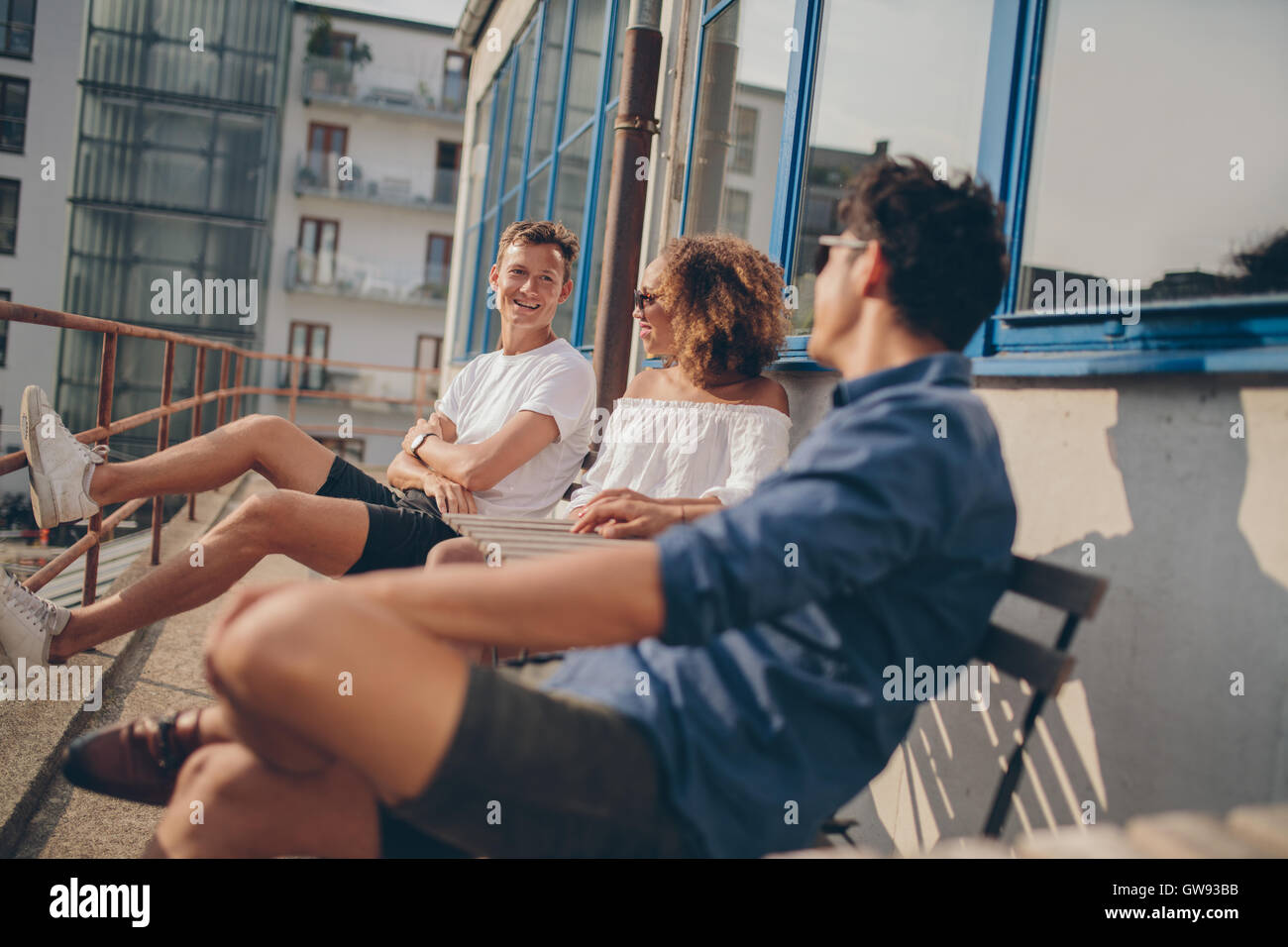 Three young friends at outdoor cafe. Multiracial group of young people relaxing outdoors at cafe table. - Stock Image