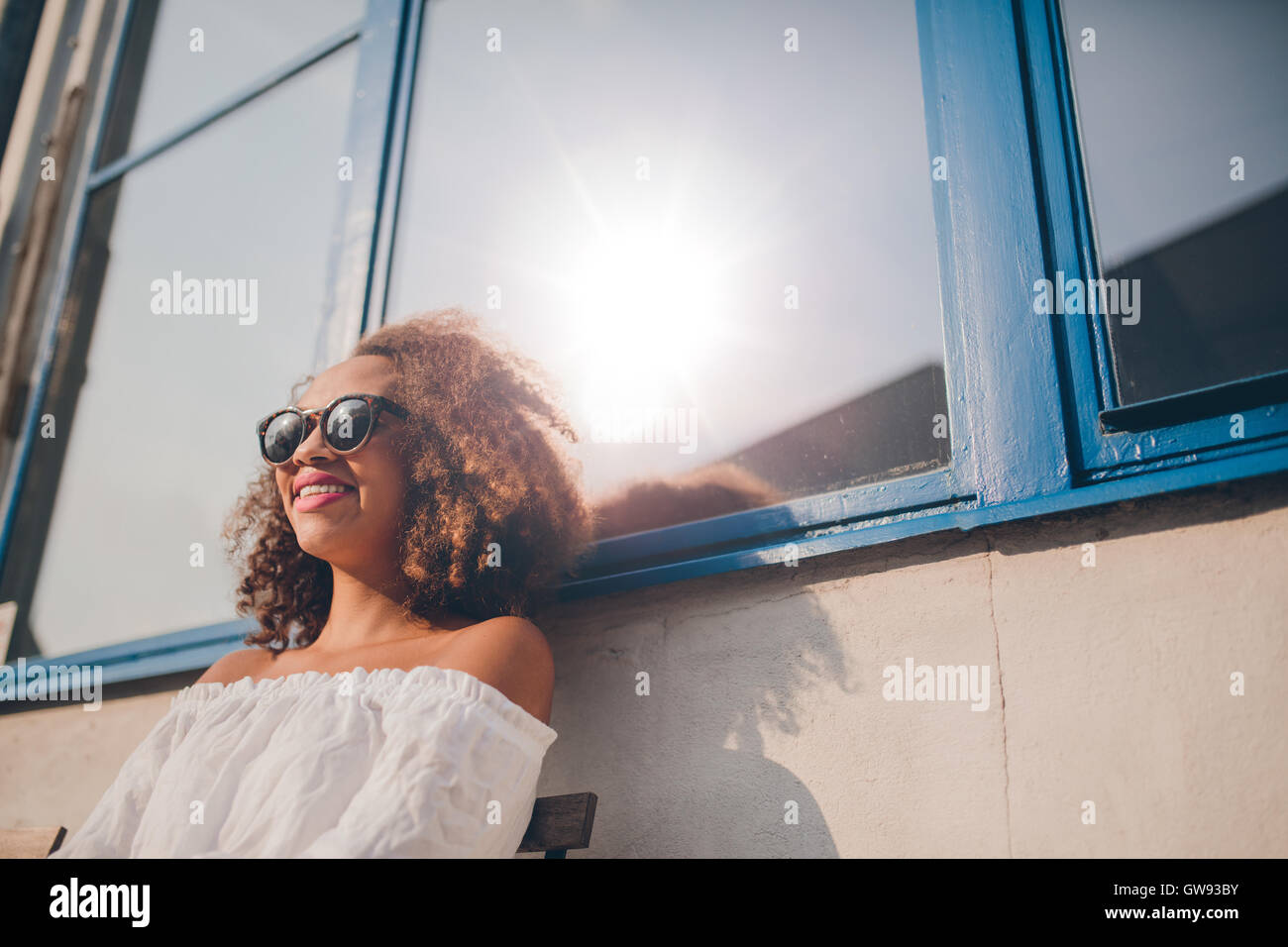 Outdoor shot of happy young african female sitting outdoors and smiling. Woman wearing sunglasses sitting outside Stock Photo