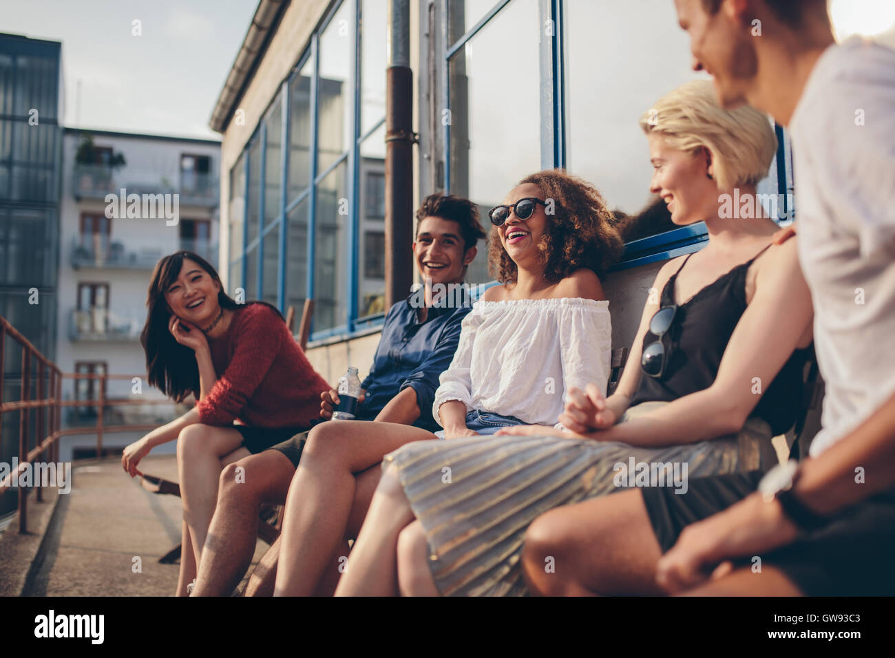 Multiracial group of friends sitting in balcony and smiling. Young people relaxing outdoors in terrace. - Stock Image