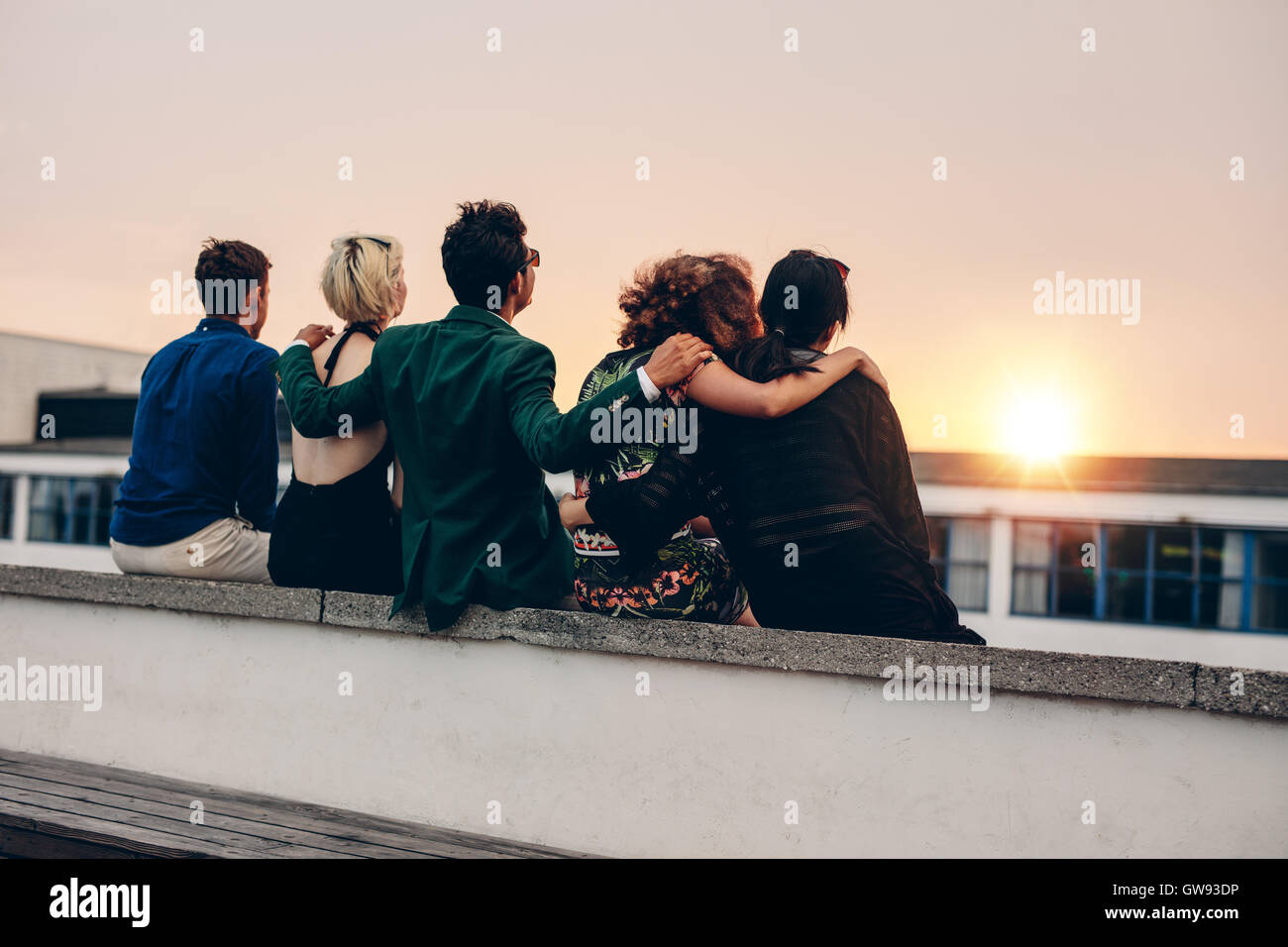 Rear view of young men and women relaxing together on rooftop and looking at sunset. Multiracial friends sitting - Stock Image