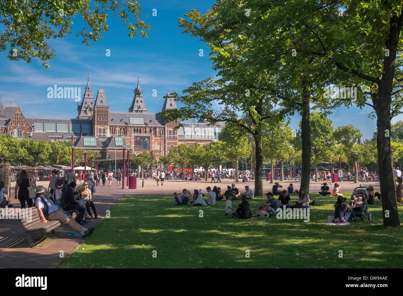 People relaxing on a warm sunny day near the landmark Rijks Museum building, Amsterdam, Netherlands - Stock Image