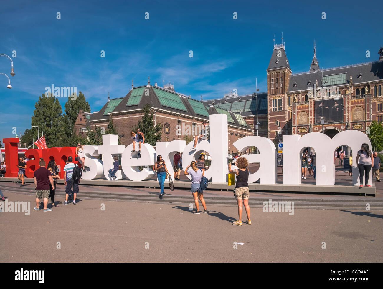 Tourists climbing and sitting on the I Amsterdam signage, Museum Quarter, Amsterdam, Netherlands - Stock Image