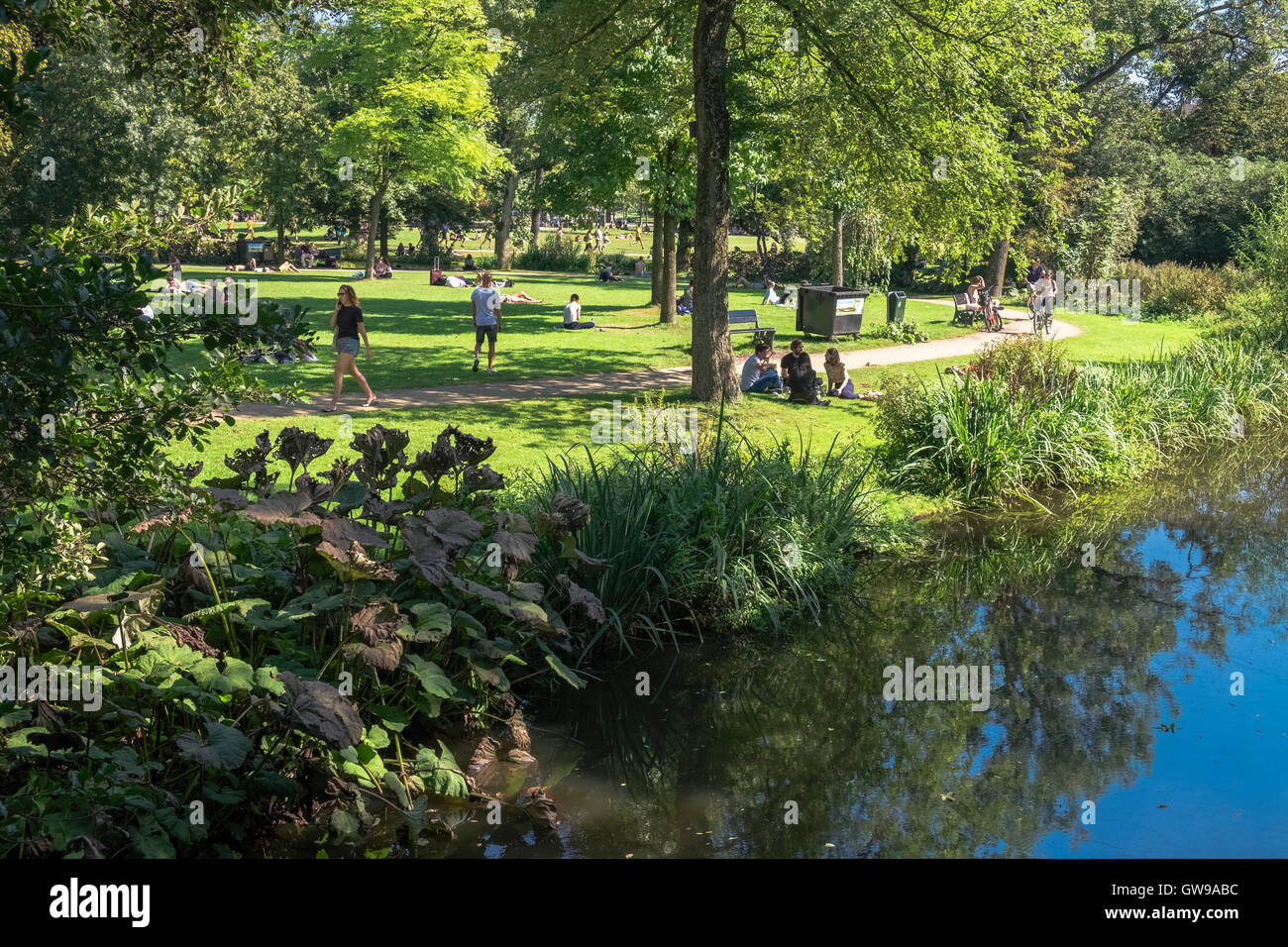 People relaxing on sunny September day in popular Vondelpark, Amsterdam, Netherlands - Stock Image