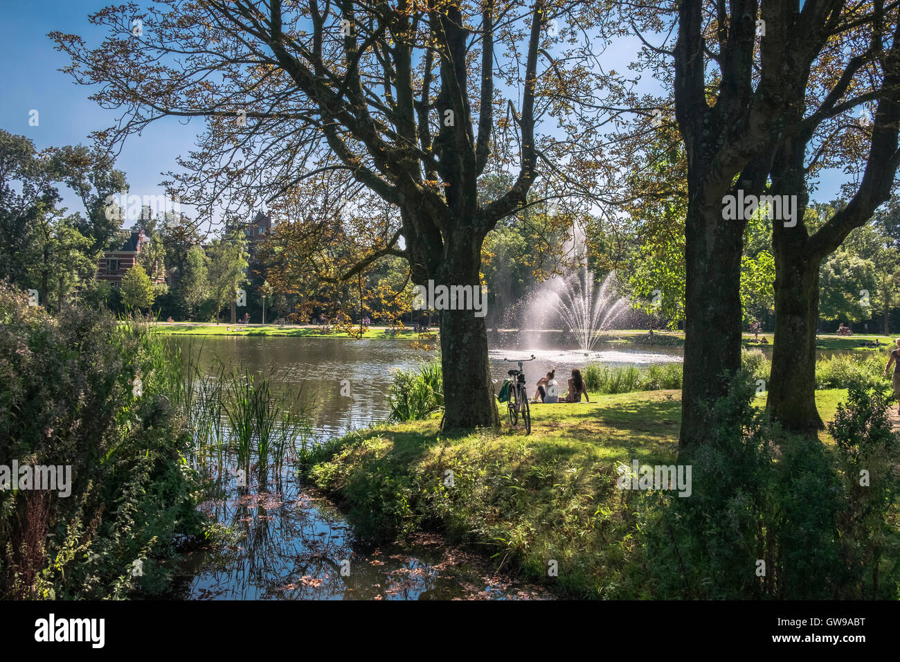Young people relaxing near lake and fountain in popular Vondelpark on sunny September day, Amsterdam, Netherlands - Stock Image