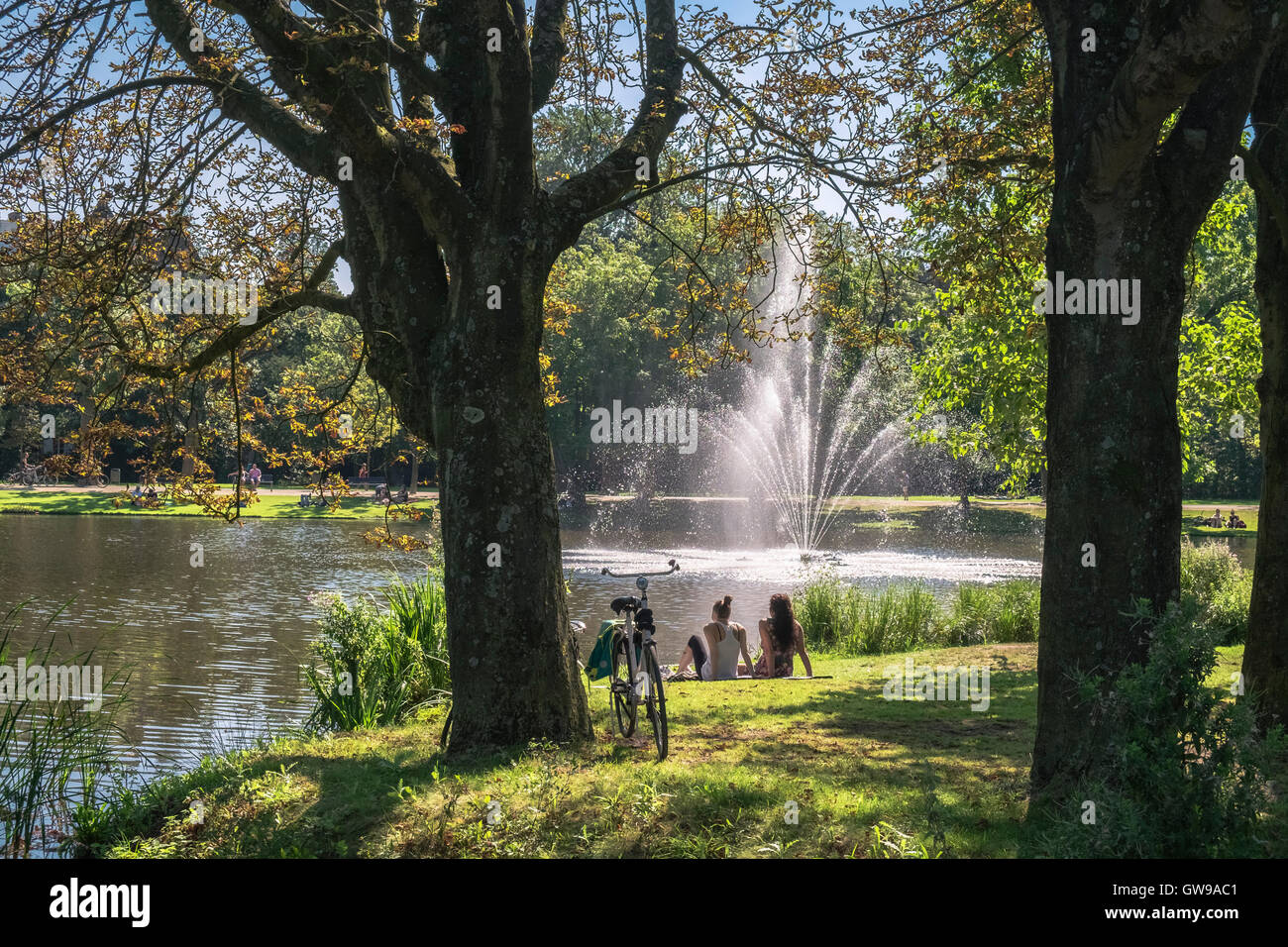 Young people relaxing near lake and fountain in popular Vondelpark on sunny day, Amsterdam, Netherlands - Stock Image
