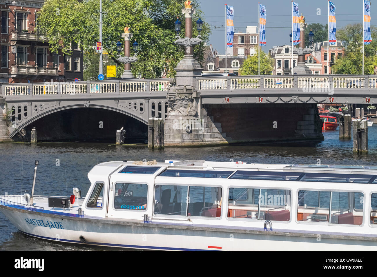 The Amstel Jade lesiure boat on the Amstel river at Blauwbrug bridge, Amsterdam, Netherlands. - Stock Image