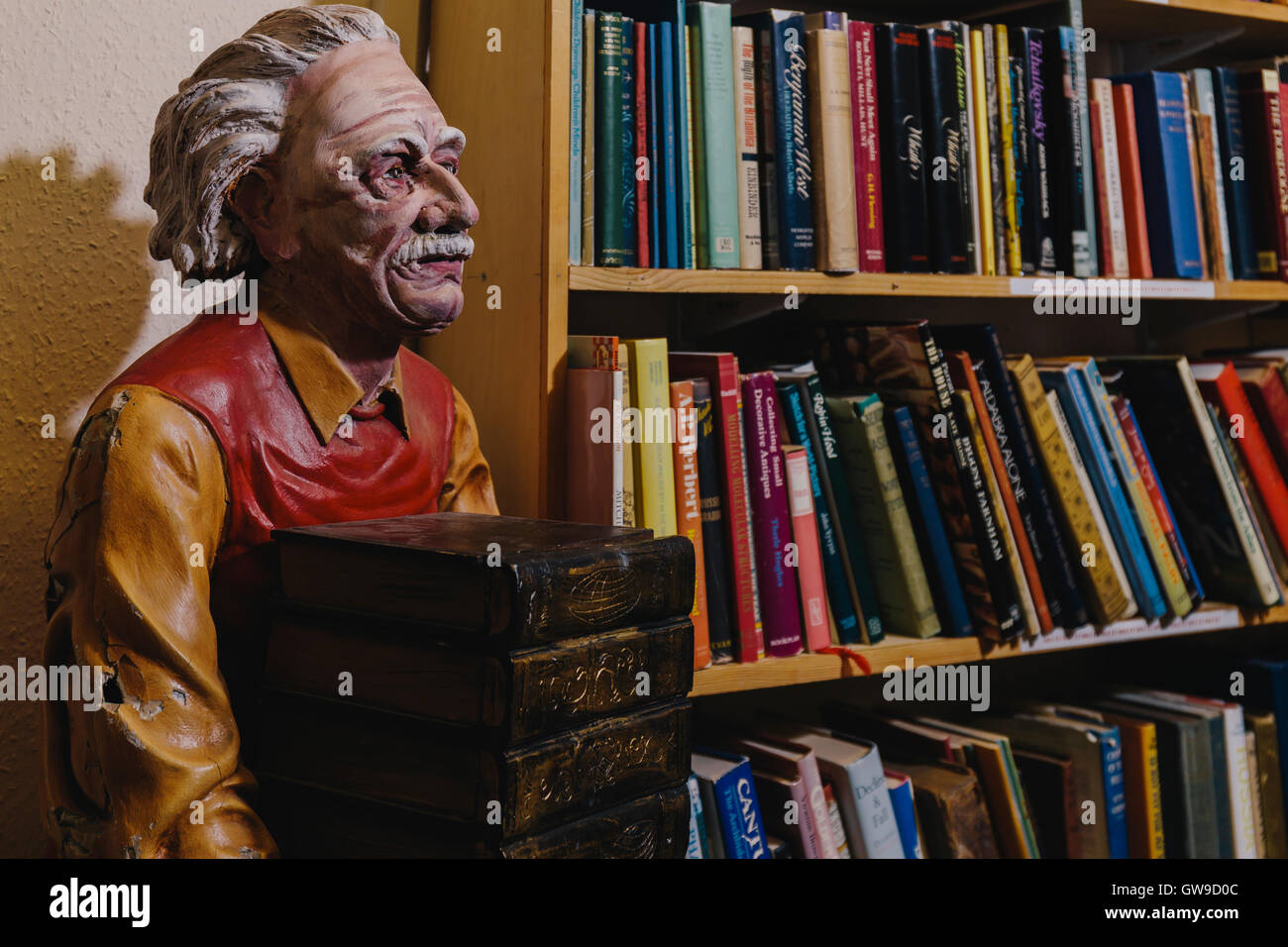 Carved figure of bookseller - Stock Image