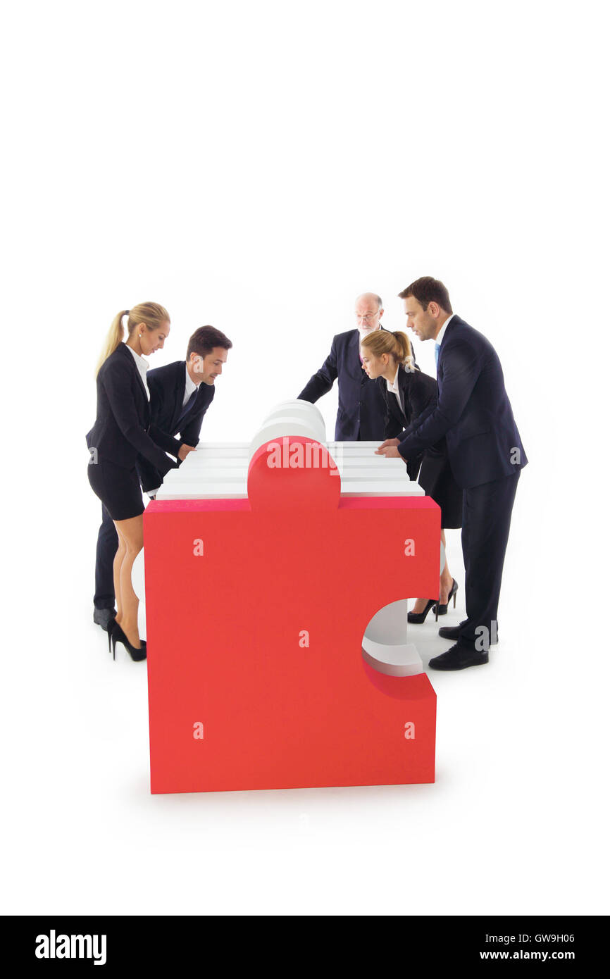 Business people team assembling puzzle isolated on white background - Stock Image