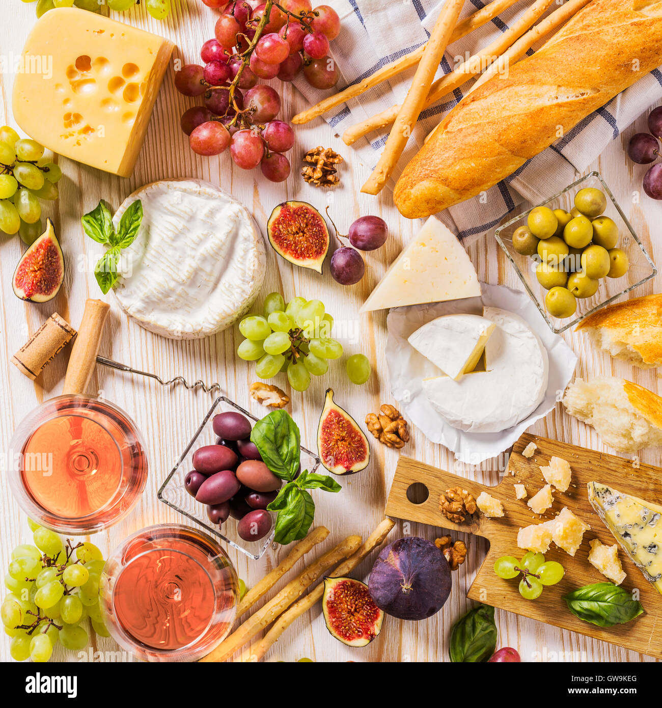 Assortment of cheeses, fruits, breads, wine and snacks on white - Stock Image