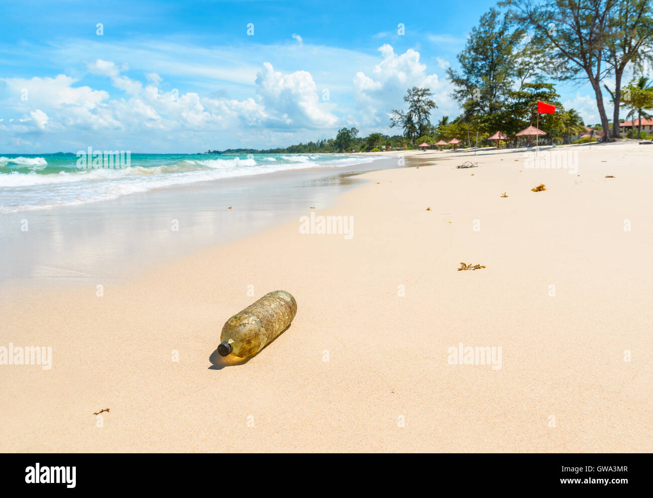 Old plastic bottle on a beautiful tropical beach in Indonesia. Pollution concept. - Stock Image