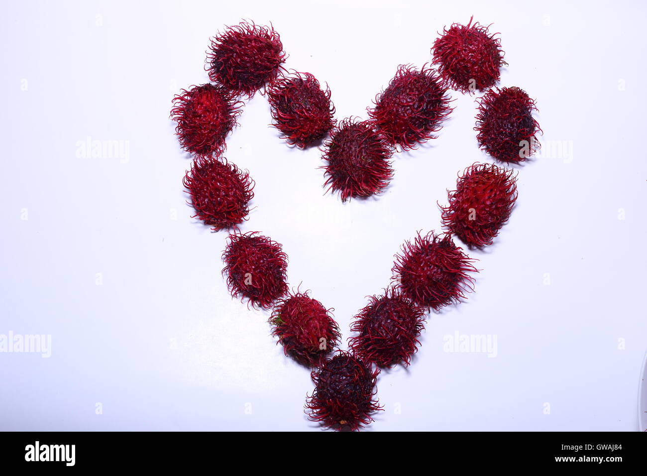 Heart with rambutan against a white background - Stock Image