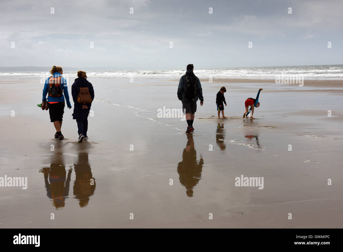 Rear view of family walking on the beach at Tywyn in Mid Wales - Stock Image