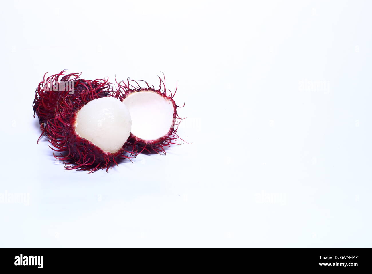 Open rambutan against a white background - Stock Image