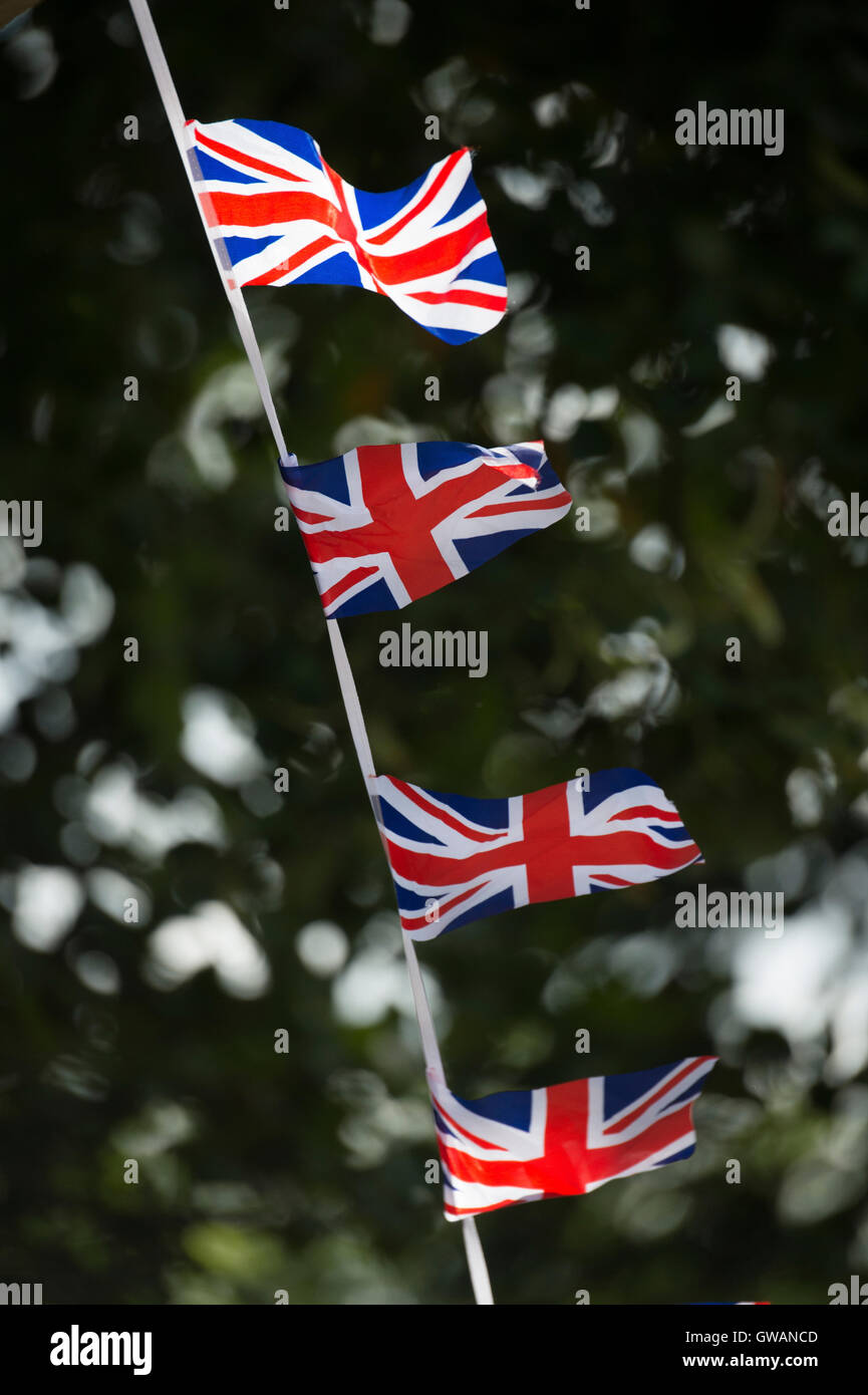 Union flags used as bunting at a cycling event, UK. - Stock Image