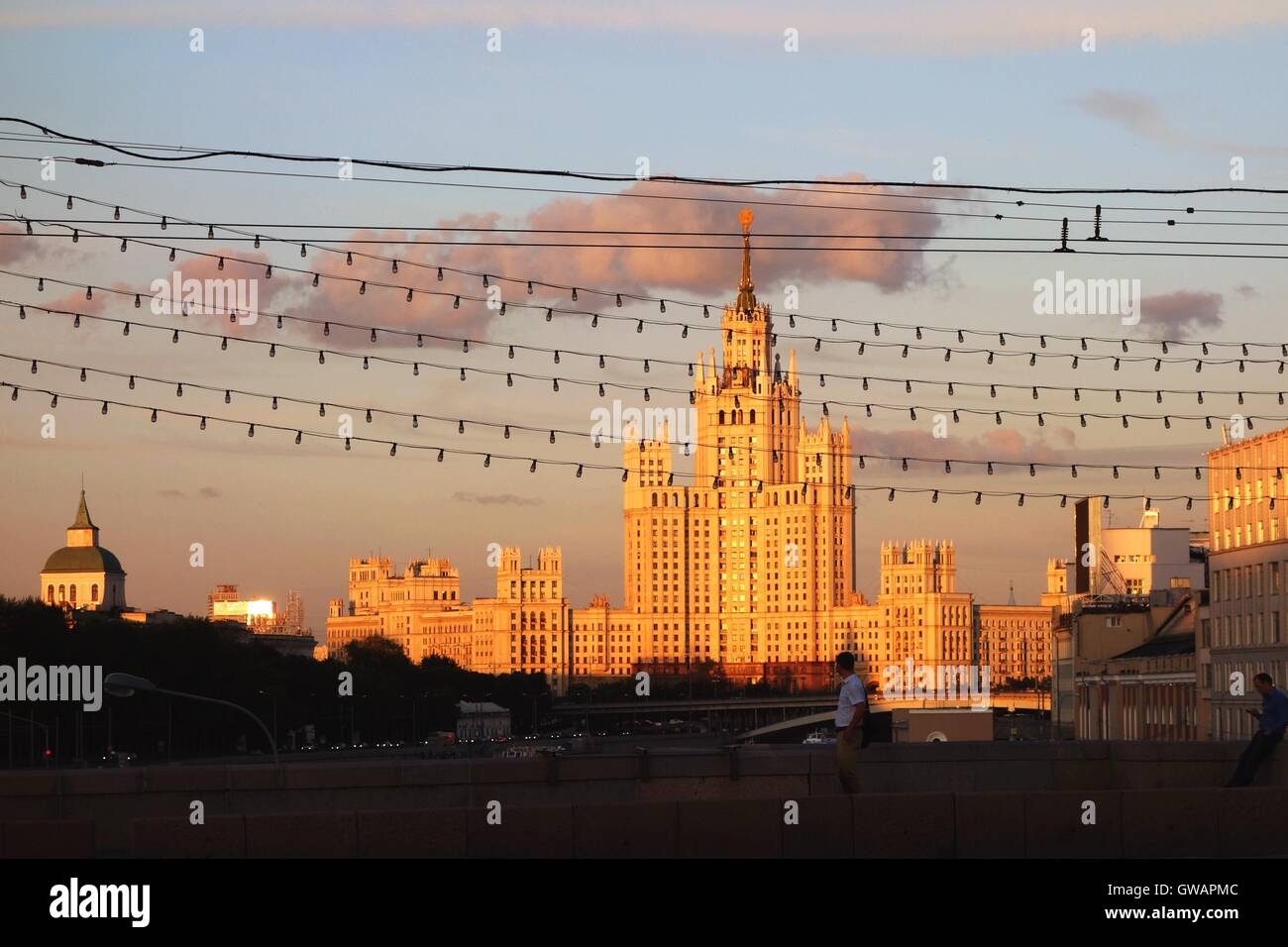 View from across the river at the Kotelnicheskaya Embankment office building covered in sunlight - Stock Image