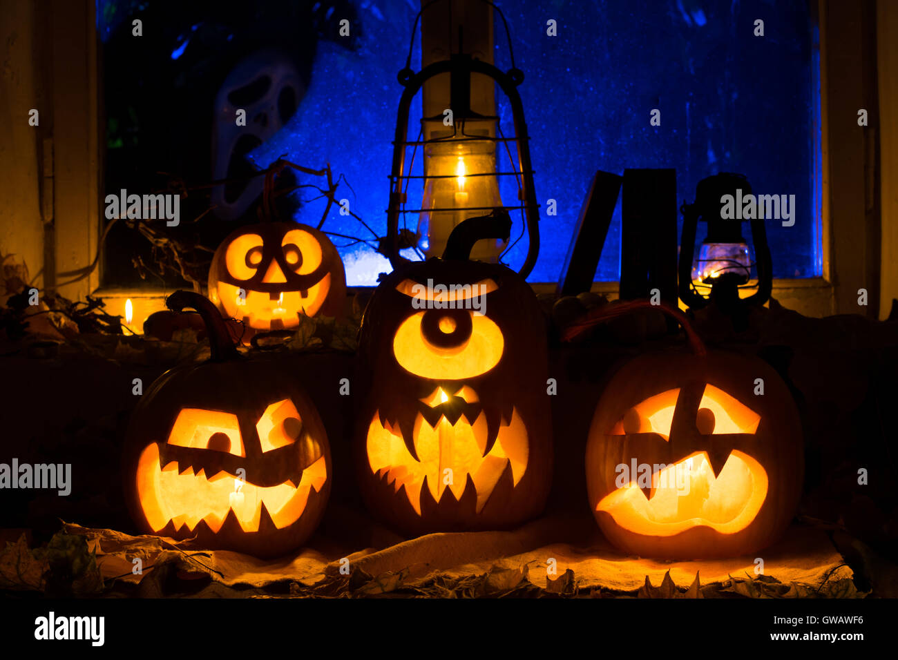 Photo composition from three pumpkins on Halloween. Embittered, the Cyclops and frightened pumpkins against an old - Stock Image