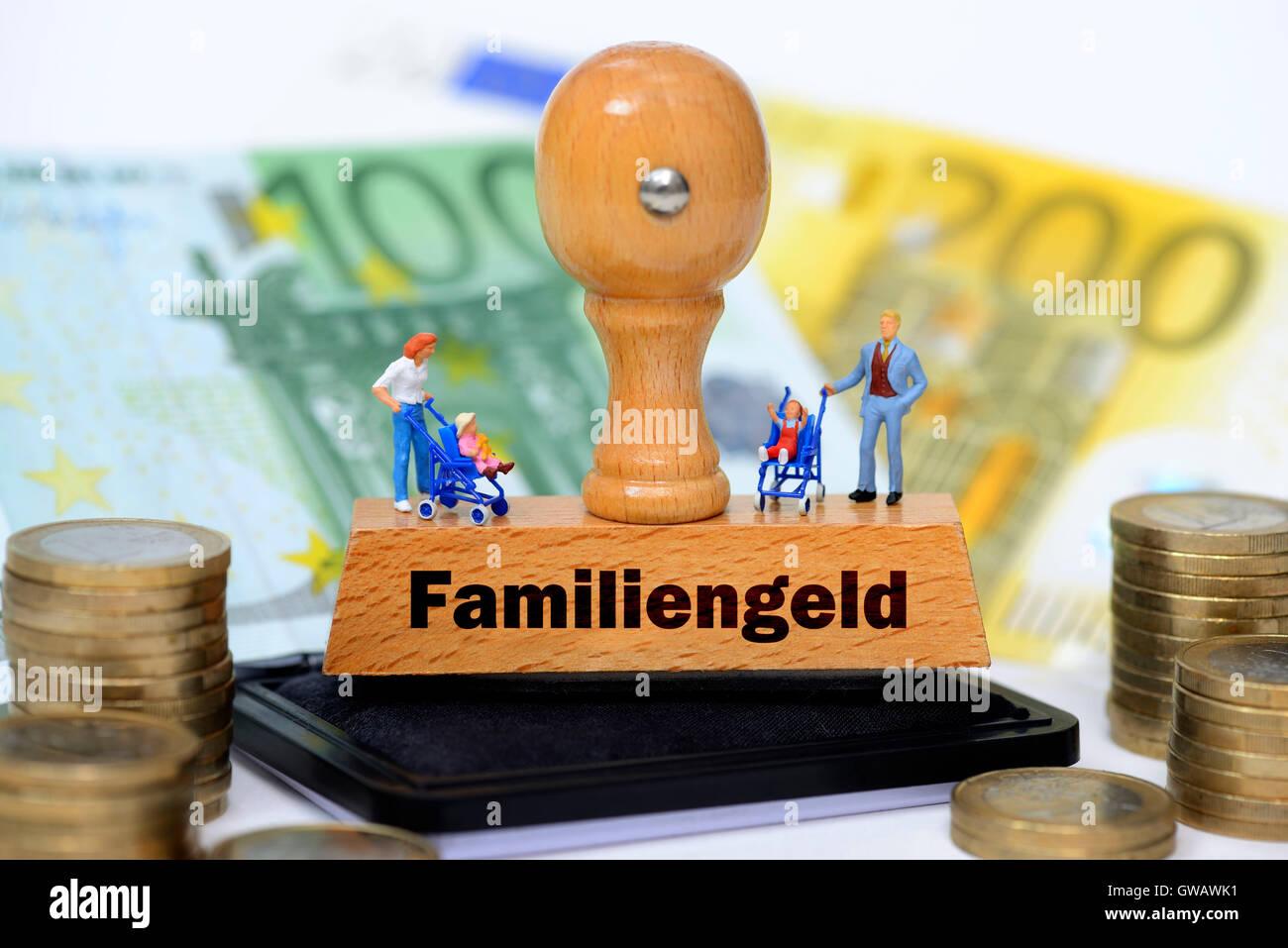 Miniature figures on a stamp with the label family money, Miniaturfiguren auf einem Stempel mit der Aufschrift Familiengeld - Stock Image