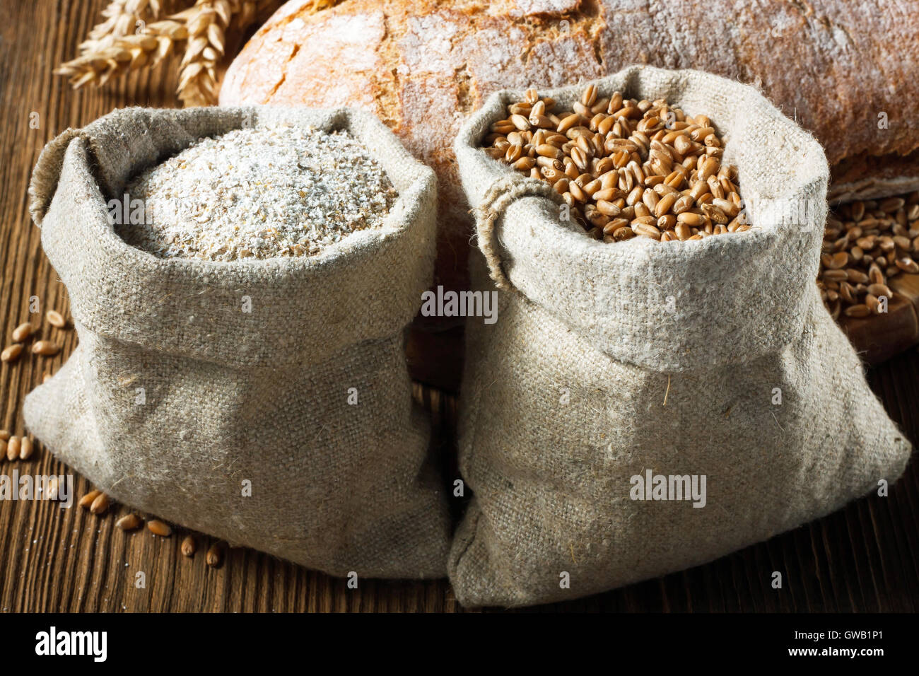 Wheat and wholemeal flour in small bags on wooden table - Stock Image
