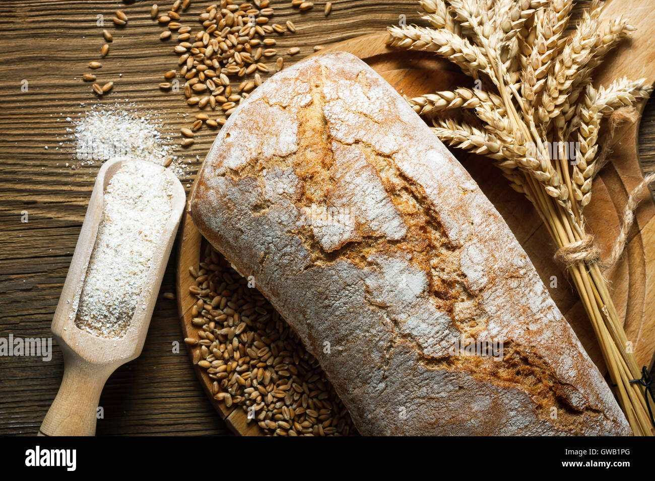 Homemade loaf of bread with ingredients on wooden table - Stock Image