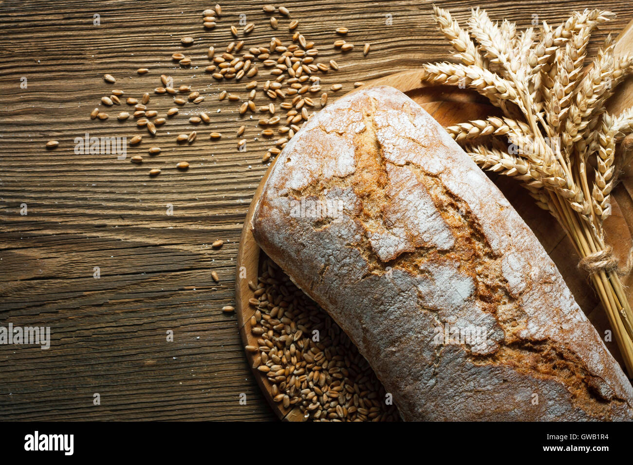 Homemade loaf of bread on wooden table - Stock Image