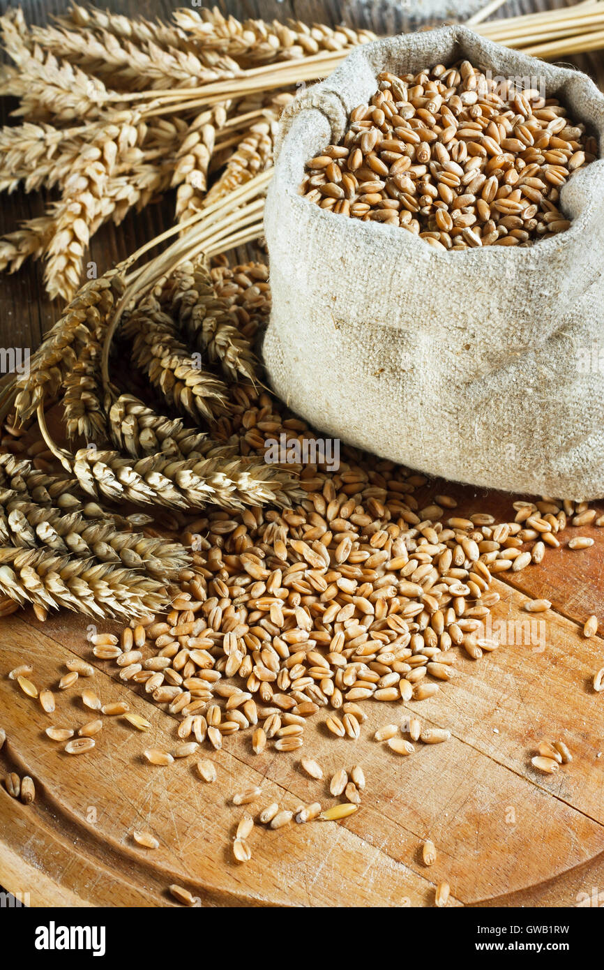 Wheat grain  in small bag on wooden table - Stock Image