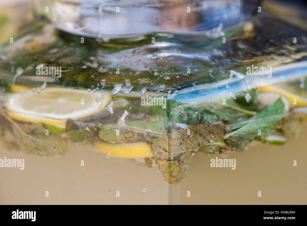 Home made lemonade in a large rectangular shape jar. Lemon and mint inside. Soft summer drink - Stock Image