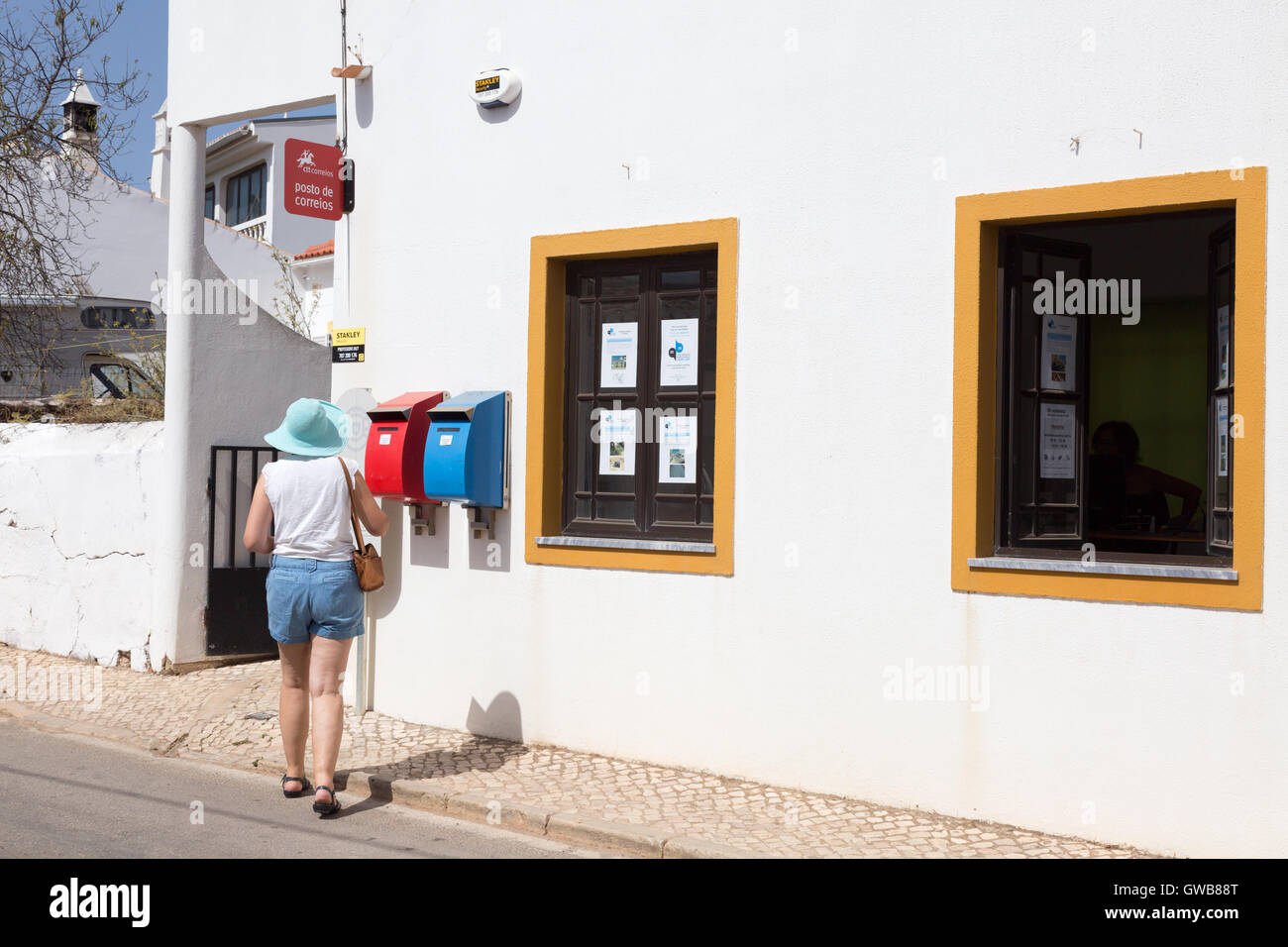 A woman posting a letter at a local village post office, the Algarve, Southern Portugal, Europe - Stock Image
