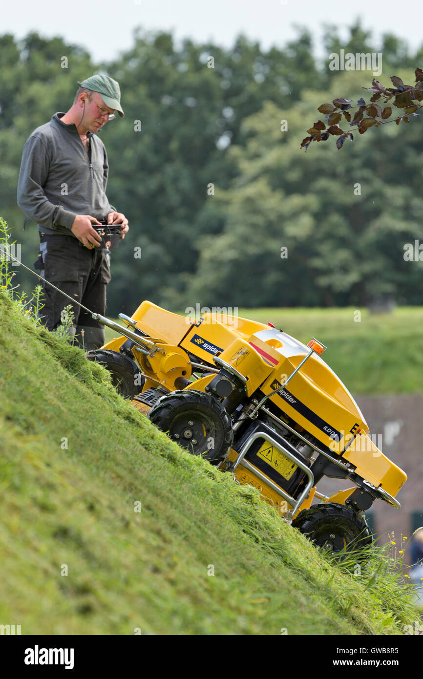 A remote control industrial grass cutter on a steep sloping city wall of the city of Naarden vesting. - Stock Image