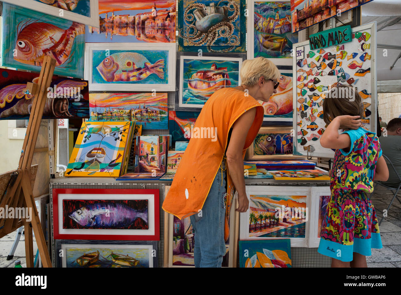 A female tourist choosing a gift at the souvenir shop of a local painter who sells canvases with marine motifs. - Stock Image