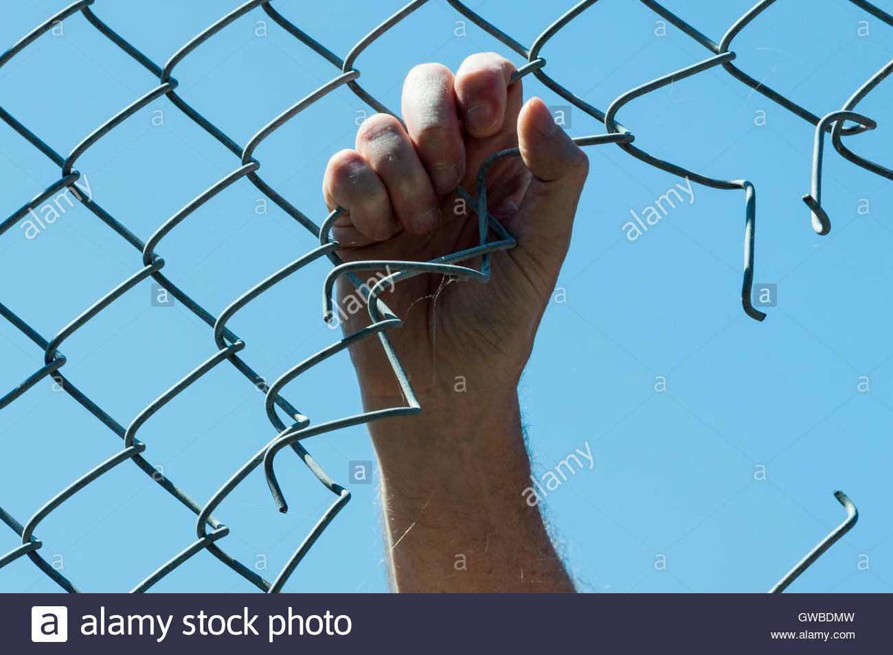 Concept image looking up at a mans hand holding onto a chain link fence with a hole cut into it - Stock Image