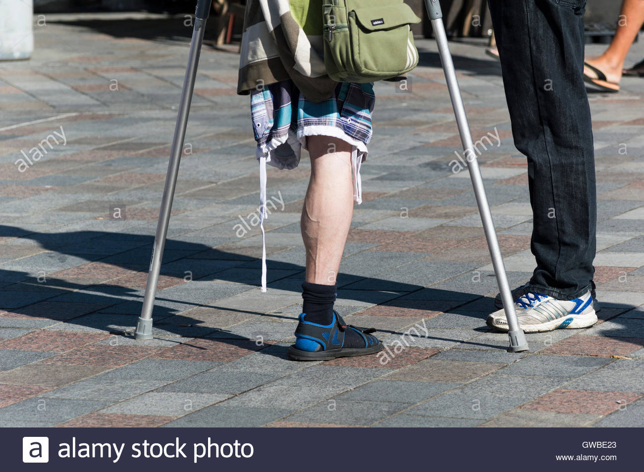 A man with one leg and crutches stands talking to another man in Salisbury Market Place, Wiltshire Stock Photo