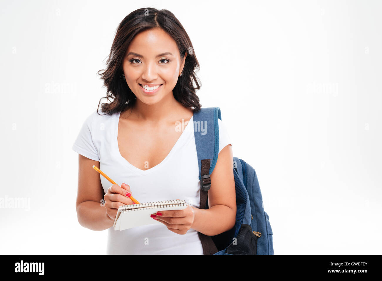 d9ca65f77c Cheerful attractive asian girl with backpack making notes in notebook  isolated on a white background